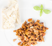 Chanterelle with garlic. Sauteed chanterelle with garlic and some white bread on a plate decorated with basil Royalty Free Stock Photo