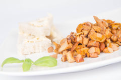 Chanterelle with garlic. Sauteed chanterelle with garlic and some white bread on a plate decorated with basil Royalty Free Stock Photos