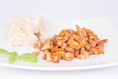 Chanterelle with garlic. Sauteed chanterelle with garlic and some white bread on a plate decorated with basil Stock Images