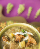 Chanterelle mushrooms soup with thyme on purple tablecloth Stock Photography