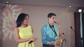 Chanteur à la peau foncée de femme de couleur et joueur de saxophone mince exécutant sur l'étape banque de vidéos