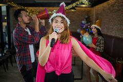 Chanteur asiatique de femme dans le chapeau du père noël avec un microphone chantant et dansant dans la fête de Noël et l'ami dan Image stock
