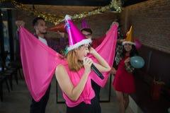 Chanteur asiatique de femme dans le chapeau du père noël avec un microphone chantant et dansant dans la fête de Noël et l'ami dan Photo libre de droits