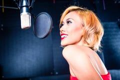 Chanteur asiatique produisant la chanson dans le studio d'enregistrement image libre de droits