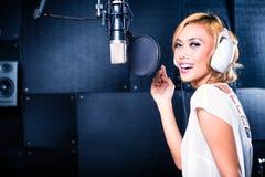 Chanteur asiatique produisant la chanson dans le studio d'enregistrement image stock