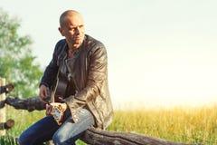 Chanteur avec la guitare sur une barrière dans le pré Image stock