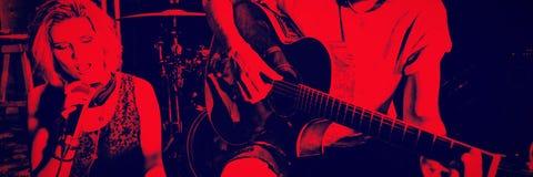 Chanteur avec le guitariste tenant le comprimé numérique à la boîte de nuit image libre de droits