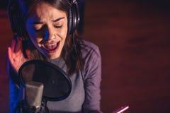 Chanteur chantant une chanson dans le studio d'enregistrement photos stock