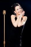 Chanteur de sourire de femme derrière le rétro microphone Photographie stock libre de droits