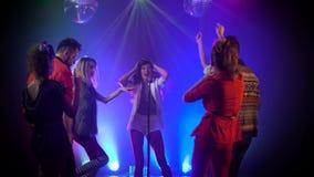 Chanteur exécutant sur l'étape comme danses d'assistance dans le studio de fumée banque de vidéos