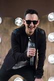 Chanteur masculin dans des lunettes de soleil avec le microphone chantant dans des projecteurs Photos libres de droits