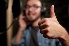 Chanteur montrant des pouces au studio d'enregistrement sonore images stock
