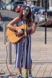 Chanteuse d'une chevelure sombre sur la rue avec des lunettes de soleil et Photographie stock libre de droits