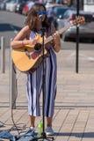Chanteuse d'une chevelure sombre sur la rue avec des lunettes de soleil et Images libres de droits