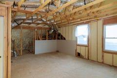 Chantier d'installer l'isolation thermique de polyurea de mousse sous les panneaux de laine de toit et les planches en bois image libre de droits