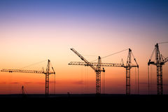 Chantier de construction avec des grues contre un ciel de coucher du soleil Image stock