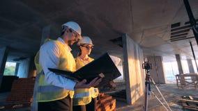 Chantier de construction avec deux constructeurs, constructeurs marchant avec des dispositions et un ordinateur portable et parle banque de vidéos