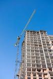Chantier de construction avec le bâtiment non fini et grue contre bleu Photographie stock