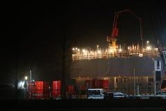 Chantier de construction avec un groupe de travailleurs de la construction qui travaillent à un bâtiment au cours de la nuit images stock