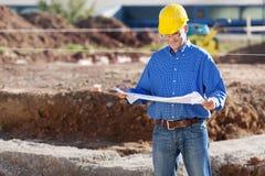Chantier de construction d'Examining Blueprint At d'homme d'affaires Images libres de droits