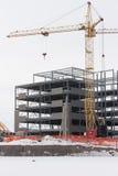 Chantier de construction et une grue en hiver Images stock