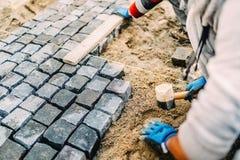 Chantier de construction industriel - travailleur étendant des pierres de granit en tant que chemin de marche Image stock