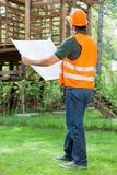Chantier de construction masculin de With Blueprint At d'architecte photographie stock libre de droits