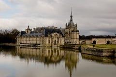 Chantilly slott i Frankrike och dess reflexion i vattnet arkivbilder