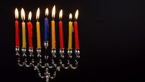 Chanukah candles all in a row. Bright, shiny multicolor candles for the Jewish holiday. All lit, isolated on a black background, horizontal view stock video footage