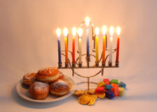 Chanukah symbols. Menorah with candles, donuts, dreidels and chocolate coins as the symbols of Chanukah royalty free stock images