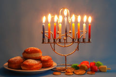Chanukah symbols. Menorah with candles, donuts, dreidels and chocolate coins as the symbols of Chanukah Royalty Free Stock Photos