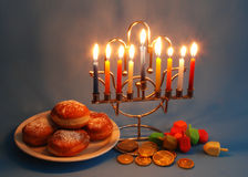Chanukah symbols. Menorah with candles, donuts, dreidels and chocolate coins as the symbols of Chanukah stock photography