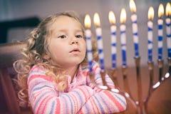 Chanukka: Kleines Mädchen betrachtet Lit-Chanukka-Kerzen stockfotos