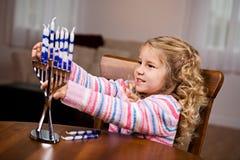 Chanukka: Kleines Mädchen, das Kerzen in Menorah setzt Stockbild