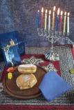 Chanukka Menorah mit brennenden Kerzen, Geschenken, Dreidel und Jelly Fill lizenzfreie stockfotos