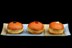 Chanukkah donuts with different filling. Various sufganiyot with different filling on a decorative plate stock images