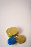 Chanukkah: Dreidel och flera Gelt chokladmynt royaltyfria bilder