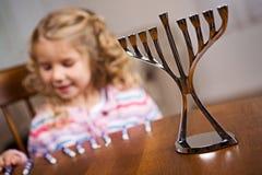 Chanukkah: Fokus på Chanukkahmenoror med flickan i baksida Arkivbild