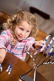 Chanukkah: Liten flicka som sätter stearinljus in i menoror royaltyfri fotografi