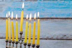 Chanukkahmenoror med stearinljus och silverdreidel Arkivfoto