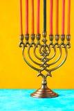 Chanukkahmenoror med stearinljus på den gula bakgrundslodlinjen Royaltyfri Foto