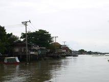 Chaophya河生态海滨木房子的生活在明媚的阳光天,社区,寺庙和停车处小船 免版税库存照片