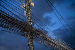 Chaos of cables and wires on electric pole over evening sky Royalty Free Stock Image