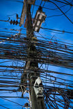 Chaos of cables and wires on electric pole over evening sky Stock Images