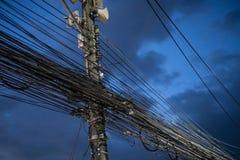 Chaos des câbles et des fils sur le poteau électrique au-dessus du ciel de soirée Image libre de droits