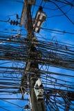 Chaos des câbles et des fils sur le poteau électrique au-dessus du ciel de soirée Images stock