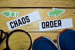 Chaos lub rozkaz naprzeciw kierunków znaków z sneakers, powiększać i eyeglasses na drewnianym, obraz royalty free