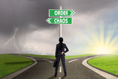 Chaos and order choice 1. Businesswoman standing on the road looking at signpost of order and chaos Royalty Free Stock Photos