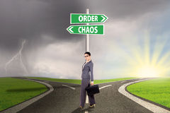 Chaos and order choice 3. Businesswoman standing on the road with signpost of order and chaos Stock Photos