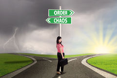 Chaos and order choice 2. Businesswoman standing on the road with signpost of order and chaos Stock Images
